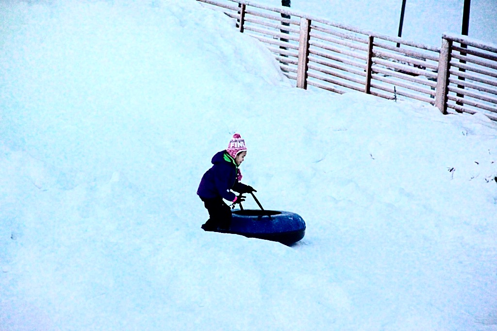 Little girl sliding downhill in Rovaniemi