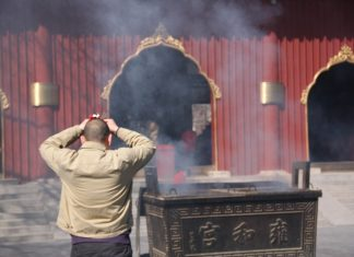 Chinese man praying in a temple