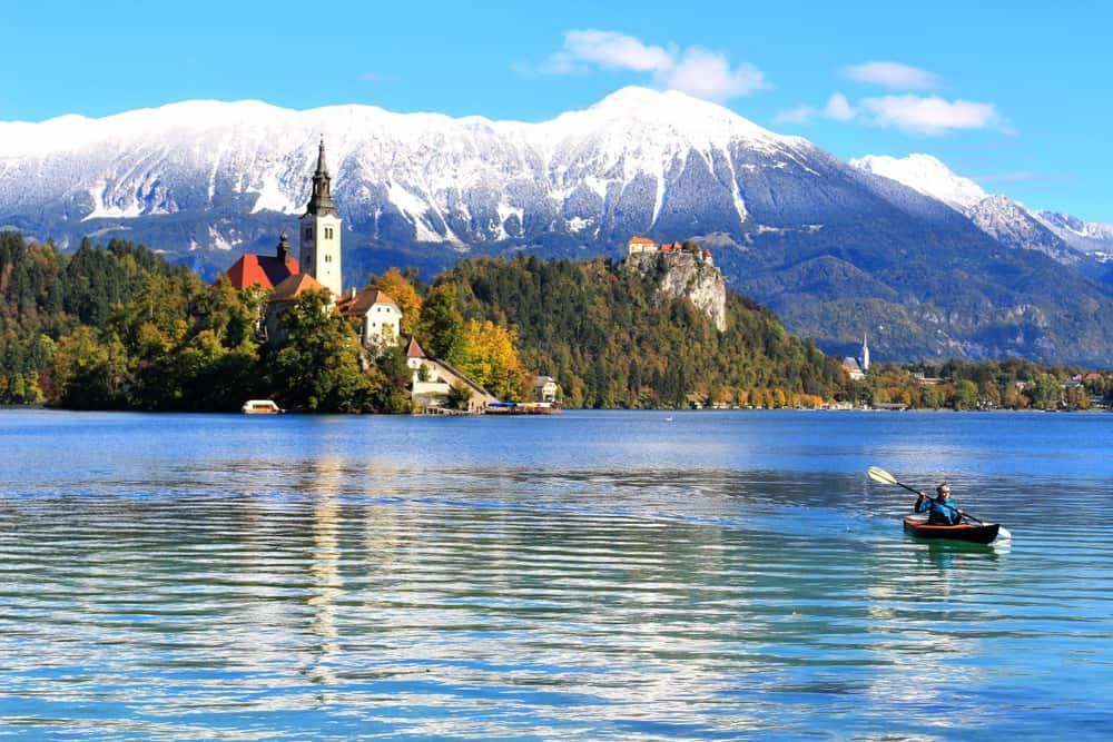 Bled church lake snow mountains, man kayaking, slovenia beautiful places